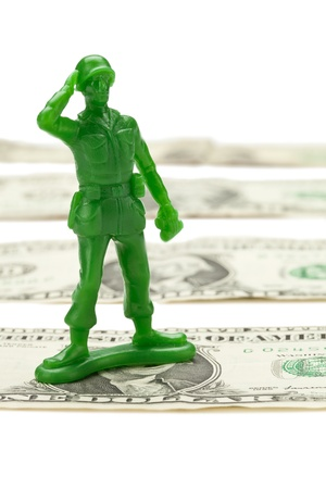 Toy soldier standing on top of a cash dollar photo
