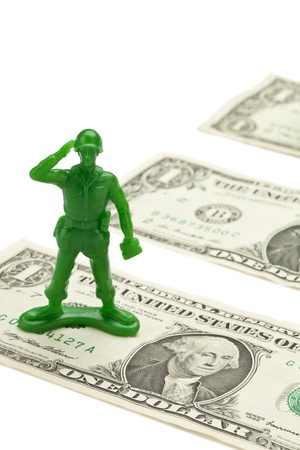 green plastic soldiers: Vertical image of a green toy soldier standing on a dollar bill with a salute Stock Photo