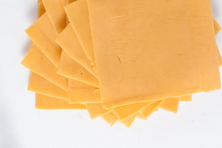 up close image: Up close image of a cheddar cheese sliced into square against white background