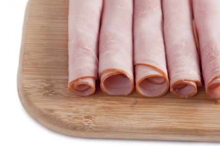 up close image: Up close image of a ham rolls on a chopping board against white background Stock Photo