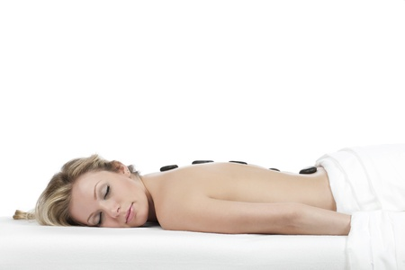Pretty woman lying while having a hot stone massage therapy on her back Stock Photo - 16963133
