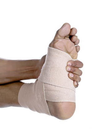 tensor: Close-up image of foot with a sprain covered by a tensor bandage isolated on a white surface