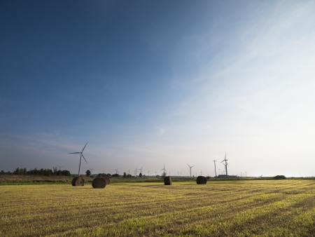 View of hay bale with wind turbine in the background. Stock Photo - 16973555
