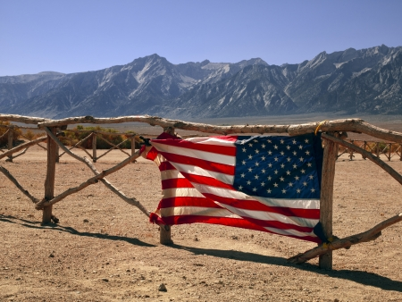 View of American flag on fence with mountains in background. Stock Photo - 16983612
