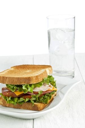 ham sandwich: Immagine di un piatto bianco con panino al prosciutto fatto in casa e un bicchiere d'acqua sul tavolo