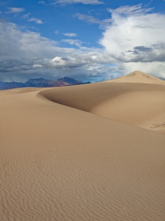 A big sand dune rises above the ground in Death Valley, USA. photo
