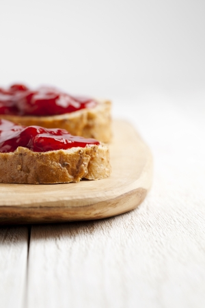 cropped image: Cropped image of a bread with strawberry jam on the wooden plate Stock Photo