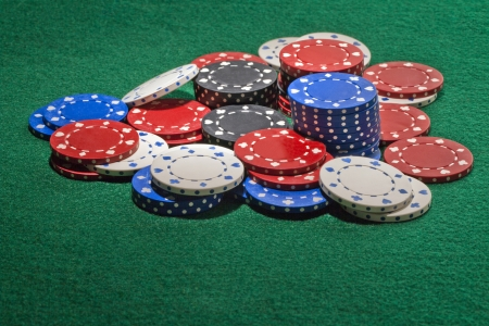 Close-up image of colorful casino chips on the green table photo