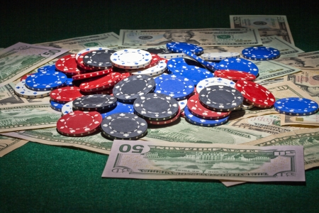 Poker chips and cash spread on a green table Stock Photo