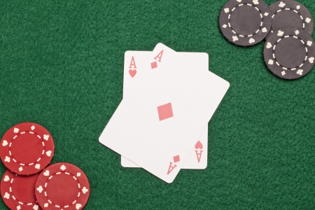 Close-up image of a casino chips and two aces on the wooden table photo