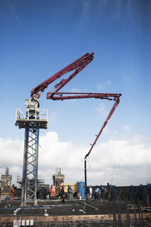 Construction crane at construction site with blue sky in the background. Editorial