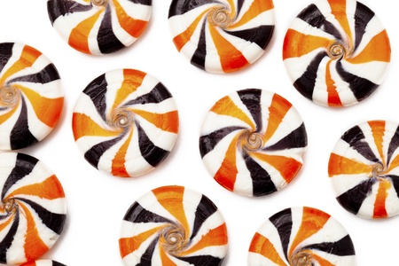 Close-up shot of colorful hard candies with swirl design over white background. photo