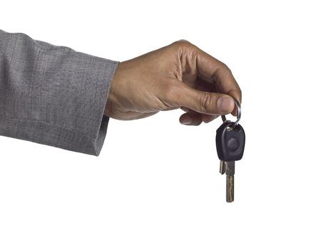 investment real state: De cerca la imagen de la llave mano humana que sostiene contra el fondo blanco