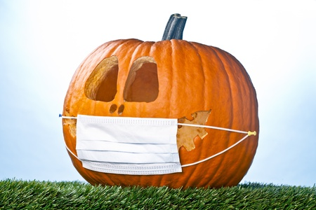 suppressed: Jack O Lantern smiling face expressing happiness suppressed by a medical face mask. Stock Photo