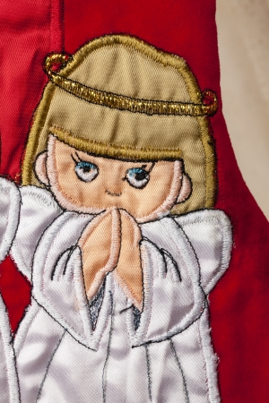 A close-up of an angel praying on a red Christmas stocking decoration