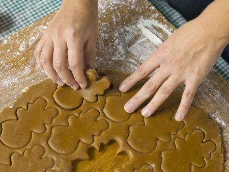 Human hand preparing gingerbread cookies at Christmas eve photo