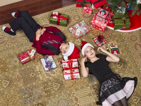 Brother and sister lying on floor near christmas tree photo