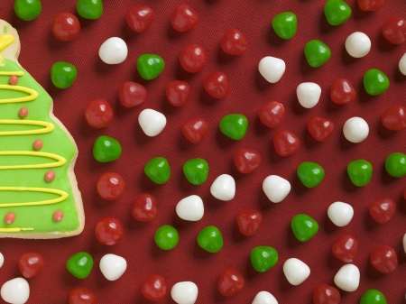 Cropped image of a Christmas tree biscuit and candies over the red background photo
