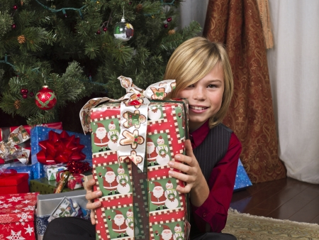 12 13 years: Close-up of a boy with his christmas gift looking at camera,