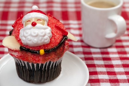 Image of a cupcake with Santa Claus miniature and coffee cup in background