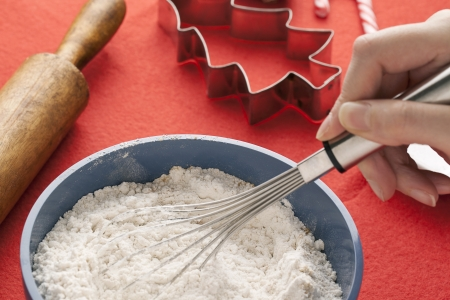 Detailed image of human hand mixing flour in plastic bowl with rolling pin and cookie cutter in background  Stock Photo - 16973480
