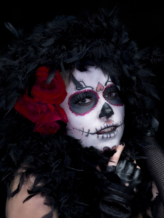 stage makeup: Close-up portrait shot of a scary woman posing in traditional sugar skull make-up against dark background