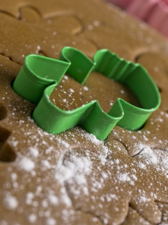 Detailed shot of plastic gingerbread cutter on gingerbread dough  photo
