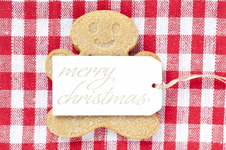 Close-up view of gingerbread man with merry Christmas tag over a checkered background Stock Photo - 16982730