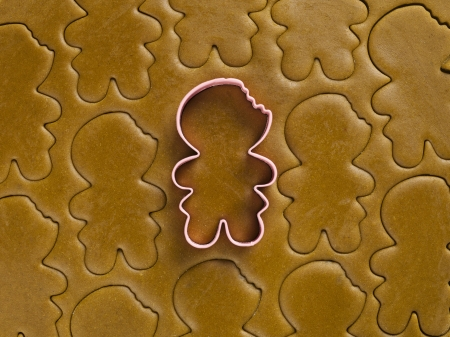 cutter: Detail view of gingerbread dough with plastic men cookie cutter