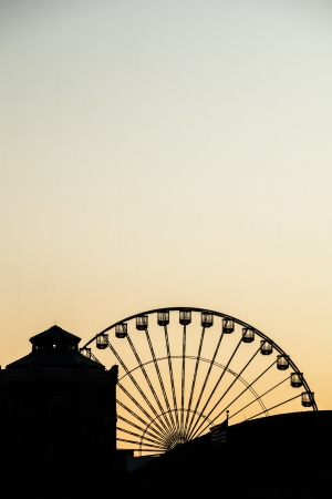 Ferris wheel at sunset in a silhouette image photo