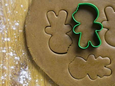 cutter: Close-up shot of gingerbread dough with cookie cutter on wooden worktop