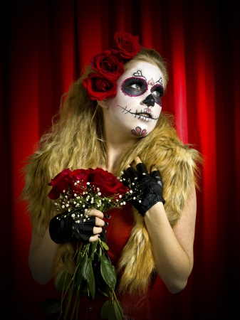 View of a woman in witch make up holding flowers and looking away  photo