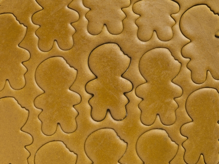 Close-up shot of gingerbread man shapes on gingerbread dough  photo