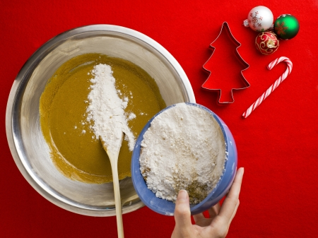Person pouring flour in chocolate syrup with cookie cutter and Christmas bauble with candy cane over red background  photo