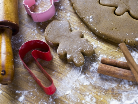 wood cutter: Detailed view of plastic cookie cutter and gingerbread cookies with rolling pin on worktop
