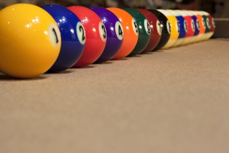 Close-up shot of pool balls arranged in a row against cushion on pool table  photo