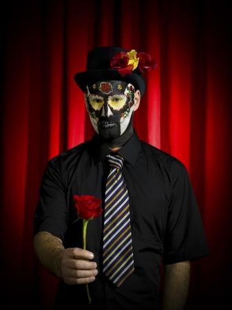 traje mexicano: Disparo Retrato de un hombre asustadizo cráneo llevaba azúcar y ofreciendo rosa sobre fondo rojo