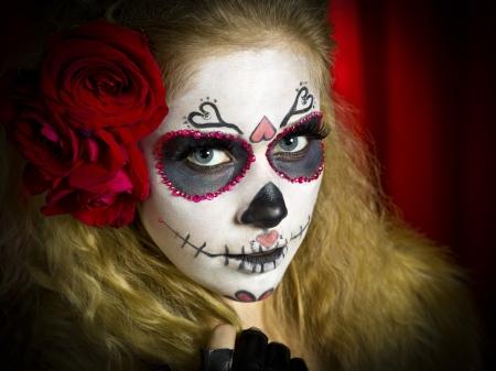traje mexicano: Retrato de tiro de una calavera de azúcar mujer vestida de miedo y rosas en el pelo