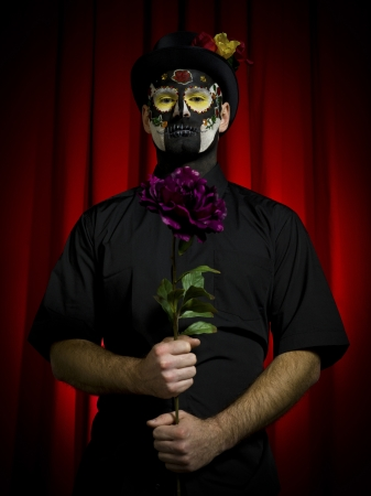 Portrait shot of a scary man wearing sugar skull posing with flower in hand over red background  photo