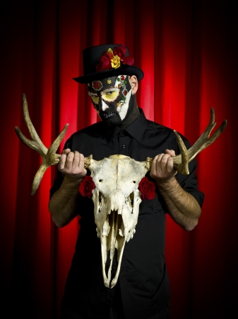 Portrait shot of a scary man wearing sugar skull posing with animal skull in hand over red background  photo