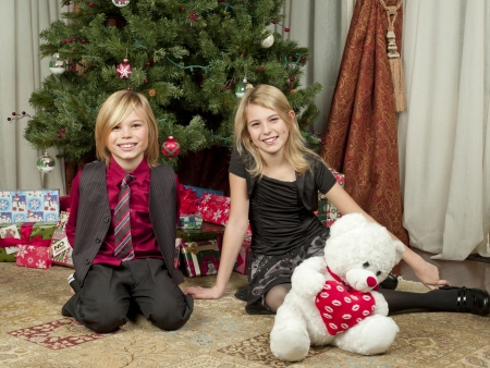 Portrait shot of happy siblings sitting side by side with teddy bear with Christmas gift box and Christmas tree in background