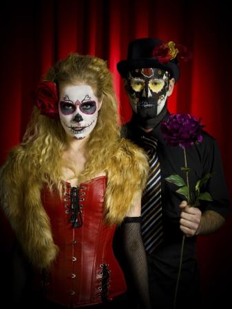 traje mexicano: Retrato de la imagen de un cráneo asustadizo buscando pareja llevaba azúcar posando sobre fondo rojo Foto de archivo