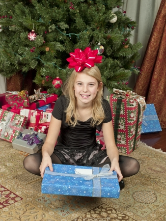 High angle portrait shot of a girl holding a Christmas gift box and bow tied on her head with Christmas tree in background
