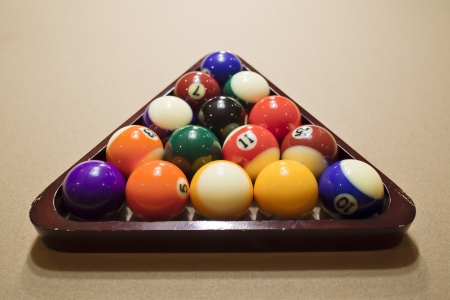 poll: Poll balls arranged in rack on pool table