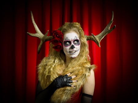 Scary female with face paint and wearing thorn and looking away over red background  photo