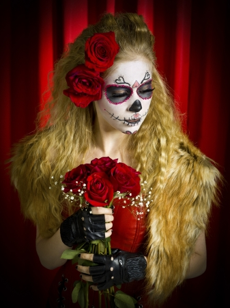 tats: Woman wearing sugar skull looking away, while holding roses