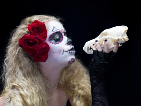 Close-up shot of a female wearing traditional sugar skull make-up and holding animal skull against ark background  photo