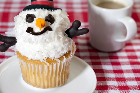 A snowman cupcake with a creamy coffee on the side of the table photo