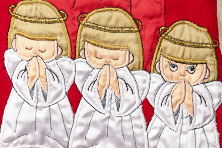 Image of three little angels with a red background