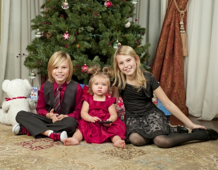 12 13 years: Portrait shot of happy brother and sisters sitting on floor with Christmas tree in background  Stock Photo